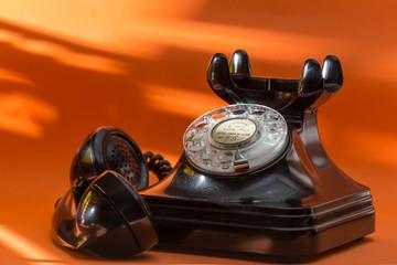 old telephone of black color, retro telephone on orange background