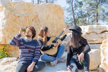 Fête de la musique Jeunes gens s'amusant en faisant la fête avec un musicien qui joue de la guitare durant un pique-nique original dans une carrière de pierres