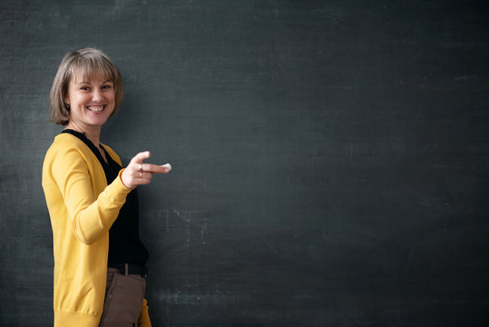 Young teacher with piece of chalk is standing near blackboard in a classroom.