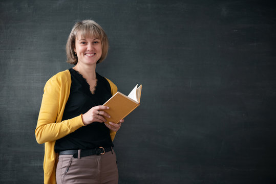 Teacher with textbook is standing near blackboard with copy space in a classroom.