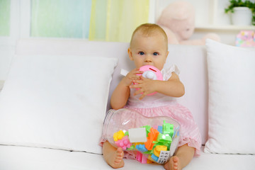 Sweet baby girl playing with toys on sofa, looking at camera