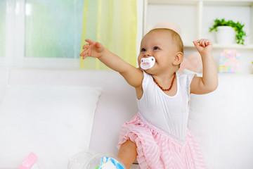 Happy baby girl pointing at something, sitting on sofa