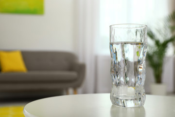Glass of water on table in room, space for text. Refreshing drink