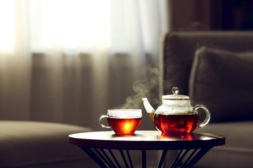 Teapot and cup of fresh hot tea on table against blurred background. Space for text