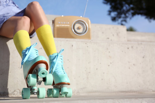 Young woman with vintage roller skates and radio sitting on stone stairs, closeup view