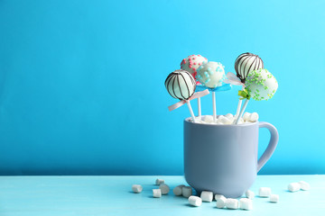 Tasty cake pops in cup with marshmallow on wooden table against light blue background. Space for text