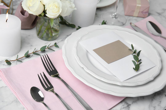 Elegant festive table setting with blank card on white marble background