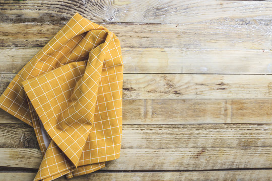 Rustic table setting from above, yellow napkin on planked wood table. Top view