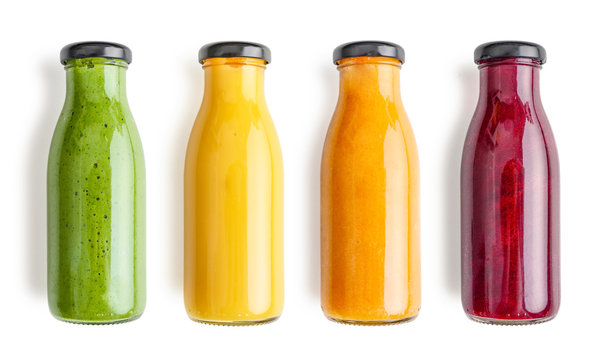Green, yellow, orange and red smoothie in glass bottles