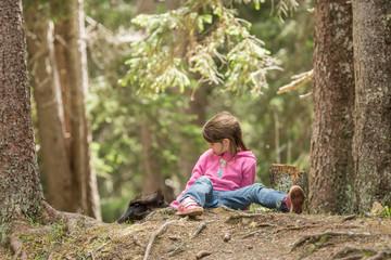 Mädchen sitzt auf Waldboden und fütter ein Eichhörnchen, Europäisches Eichhörnchen (Sciurus vulgaris)