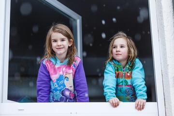 Zwei Mädchen schauen bei Schnee aus dem Fenster, Deutschland
