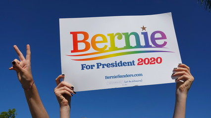 """A teen's hands hold up a """"Bernie for President 2020"""" sign into a blue sky, while another girl flashes a victory sign. Photo taken in Vista, CA / USA on October 11, 2019."""