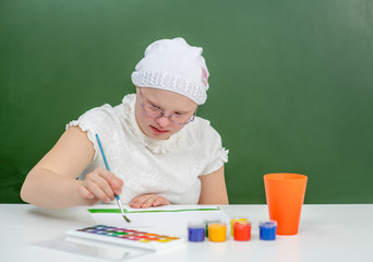 Girl with Down Syndrome draws at school