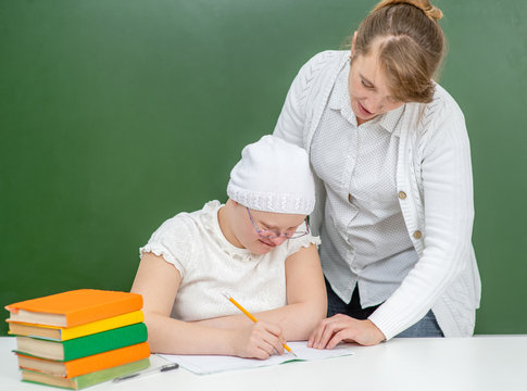 Teacher helps young girl with Down Syndrome at school