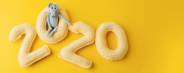 Happy New year concept. 2020 knitted yallow numbers with the symbol of the year the rat on a yellow background. Seasonal funny decoration, holiday symbol, party, monochrome