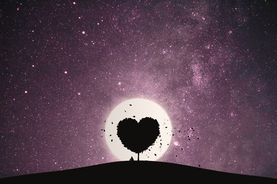 Heart shape of big tree and alone man sitting on a mountain under love tree landscape with fantasy night sky and full moon. Stunning views at lonely nights.
