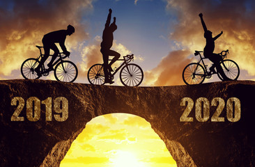 Three cyclists ride a road bicycle at sunset. Forward to the New Year 2020.