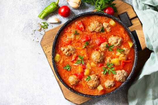 Spanish and Mexican food - Albondigas. Hot stew tomato soup with meatballs and vegetables. Top view on a flat lay. Free space for your text.