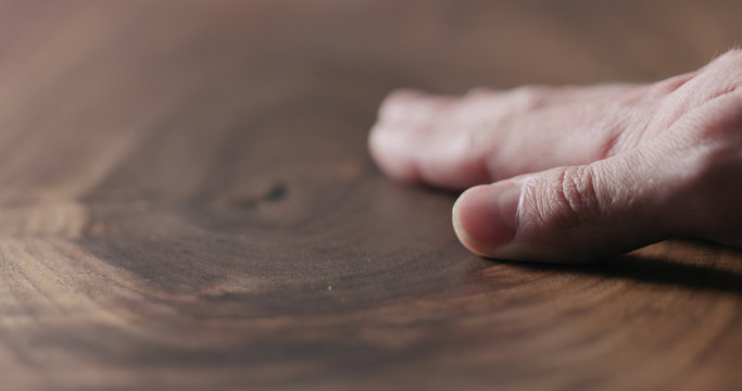 man hand touch oil finished black walnut wood surface