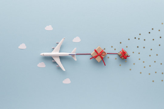 Christmas composition. Airplane flying in sky star gift clouds top view background with copy space for your text. Flat lay.