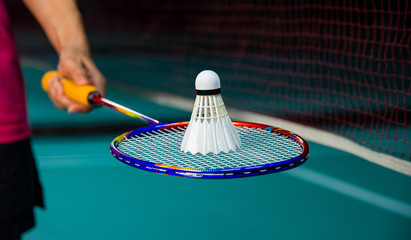 Woman Badminton player holding racket with Badminton shuttlecock on top with blurred net and badminton court background.