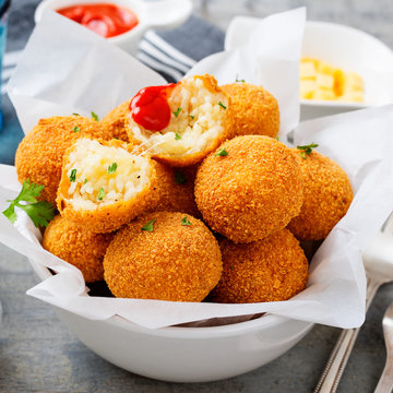 Homemade Fried Risotto Arancini stuffed with cheese, served with tomato sauce.