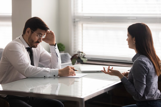 Confused male hr manager listening to female job applicant.