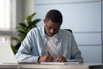Focused mixed race entrepreneur signing document or contract.