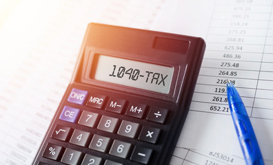 Word 1040 Tax on calculator. Business and tax concept.