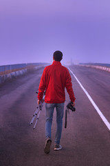 A man walks along an asphalt road with a camera and a tripod on an foggy morning, back view.