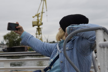 Gdansk, Poland - September 2019: A girl in a hat on the deck of a ship takes a selfie using a smartphone. A girl photographs herself against the background of ships in the port.