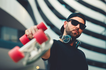Young man with headphones around neck wearing hat and sunglasses holding a skateboard in his hand and posing in the city.