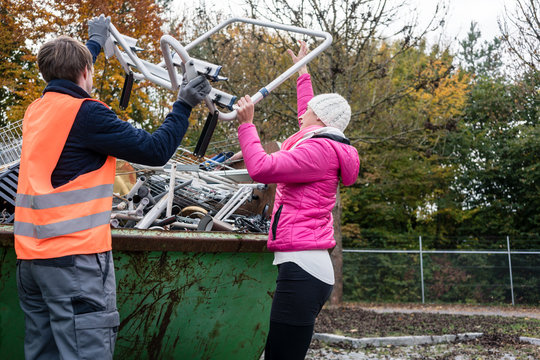 Woman putting scrap metal in container to be recycled