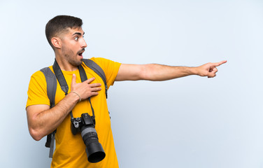Young photographer man pointing finger to the side