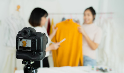 Beautiful asian woman blogger showing clothes in front of camera to recording vlog video live streaming at her shop. Business online influencer on social media concept. Online Selling. Online Shopping