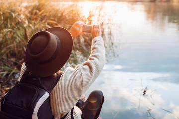 Tourist with backpack taking photos using smartphone of river at sunset. Woman travels admiring autumn nature