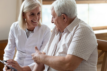 Elderly man patient and middle-aged nurse talking indoors