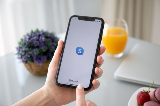 Woman hand holding iPhone 11 with calling Skype application