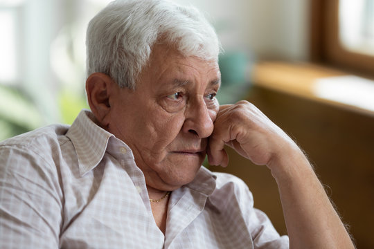 Sad grandfather put head on hand lost in thoughts