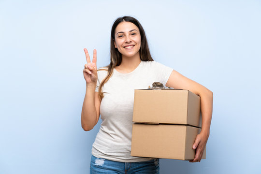 Young delivery woman over blue brick wall smiling and showing victory sign