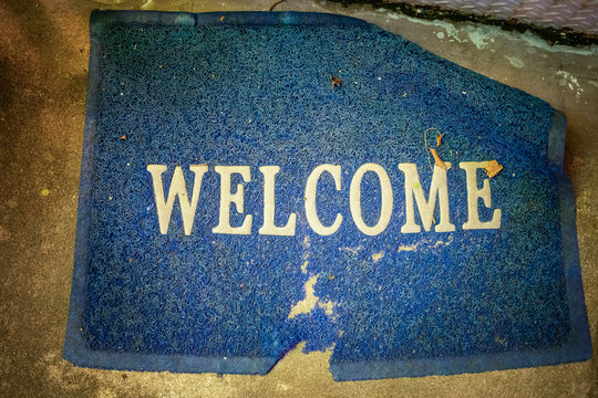 welcome Mat at the entrance, dirty old worn and worn to the holes, blue, shooting from above, close-up