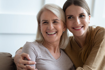 Close up photo adult daughter cuddles old mother