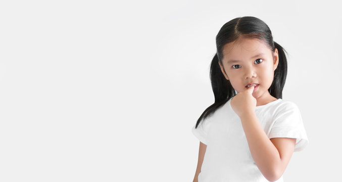 Asian child cute or kid girl nail biting on finger and smiling with anxious or thinking enjoy on preschool or 5 years old and wear white T-shirt and white background isolated with copy space