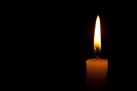 Horizontal photo of lighted candle isolated on black background. Copy space. Close up.