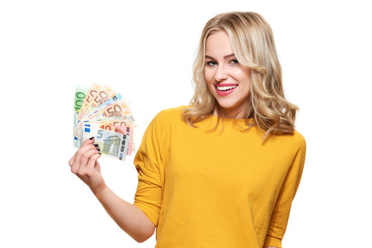 Young pretty woman in yellow sweater holding bunch of Euro banknotes, looking at camera and smiling, isolated on white background.