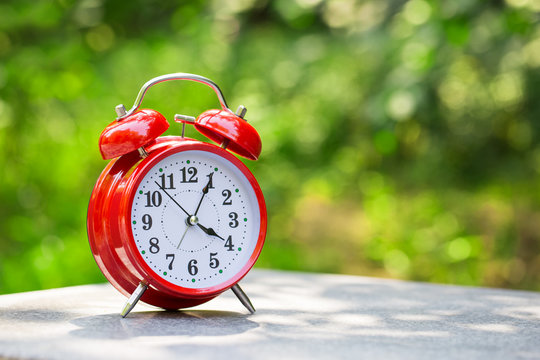 Red alarm clock. Image of Spring Time Change. Vintage Alarm Clock Outdoors. Summer back concept.