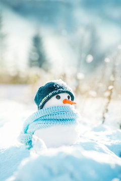 Little snowman made of snow in a knitted hat and a blue scarf on a background of a winter snowy landscape on a sunny frosty day.