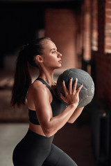 Slim flexible female in black sportswear do exercises in fitness gym. Brickwall background