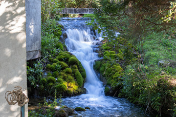 Fotobehang Watervallen Small waterfall next to the old house in a yard in village Martin Brod in Bosnia and Herzegovina