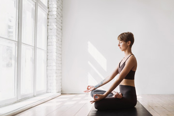 Young woman meditating at class. Beautiful girl practicing yoga at home. Harmony, balance, meditation, relaxation, healthy lifestyle concept
